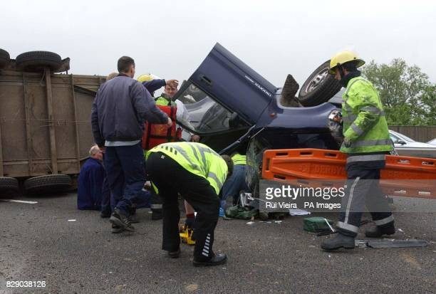 Emergency service personnel tend the occupants of a 4x4 vehicle which was towing a trailer of cows when it overturned on the M1 near Nottingham...