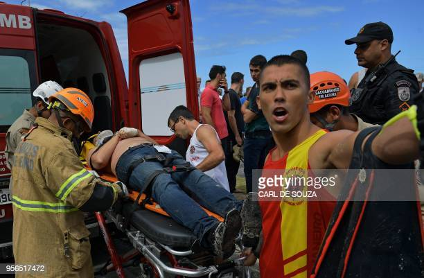 Emergency services and lifeguards attend an injured man who was involved in a helicopter crash in Barra de Tijuca Rio de Janeiro Brazil on May 9 2018...