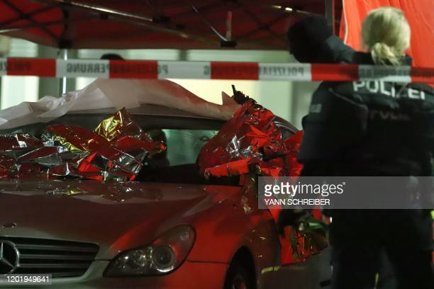 Emergency services and police work at the scene of a shooting in Hanau western Germany on February 20 2020 At least eight people were killed in two...