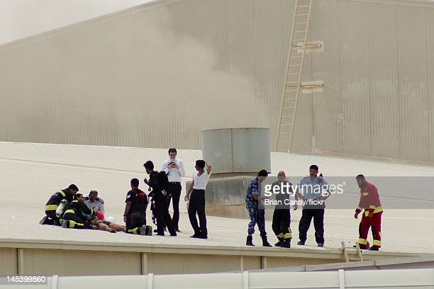 Emergency services attend to an injured man as they seek to rescue people trapped in a fire at the Villaggio mall on May 28, 2012 in Doha, Qatar. A...