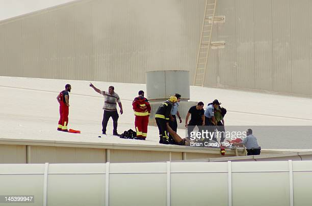 Emergency services attend to an injured man as they seek to rescue people trapped in a fire at the Villaggio mall on May 28 2012 in Doha Qatar A fire...