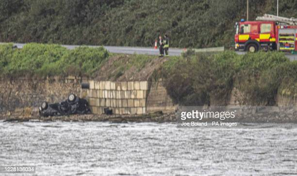 Emergency services attend to the wreckage of the car in which three people lost their lives in an accident when it entered the river Foyle near...