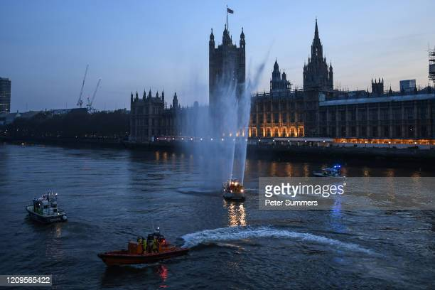 Emergency services boats are seen spraying water to applause NHS staff by the Houses of Parliament and Westminster Bridge on April 09, 2020 in...