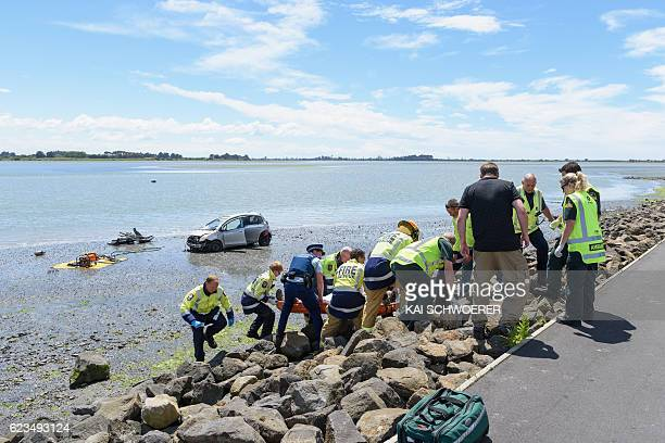 Emergency services carry an injured man from the scene where a man crashed his car into the sea on November 16 2016 in Christchurch New Zealand A...