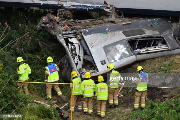 Emergency services inspect the scene following the derailment of the ScotRail train which cost the lives of three people on August 13, 2020 near...