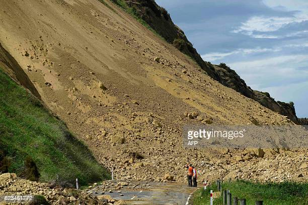 Emergency services officers inspect the damage caused to Rotherham Road near Waiau town some 90 kms to the south of Kaikoura on November 16 after an...