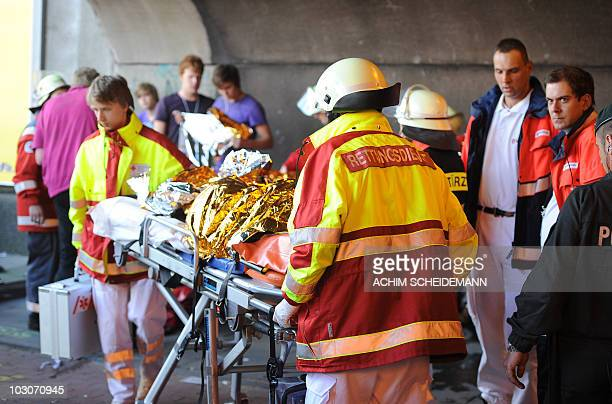 Emergency services personal work the scene after panic broke out in a tunnel during the Loveparade in Duisburg western Germany on July 24 2010 Ten...