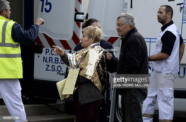 Emergency services personnel escort people away from the site of a collision on October 23 2015 in Puisseguin near Libourne southwestern France At...