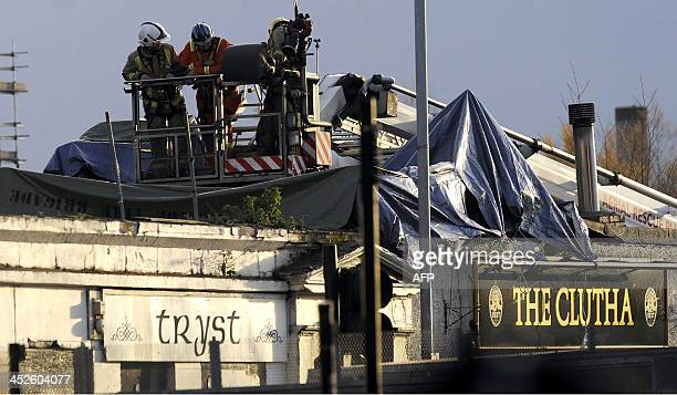 Emergency services personnel inspect the rooftop of a pub where a police helicopter crashed in Glasgow on November 30 2013 At least one person was...