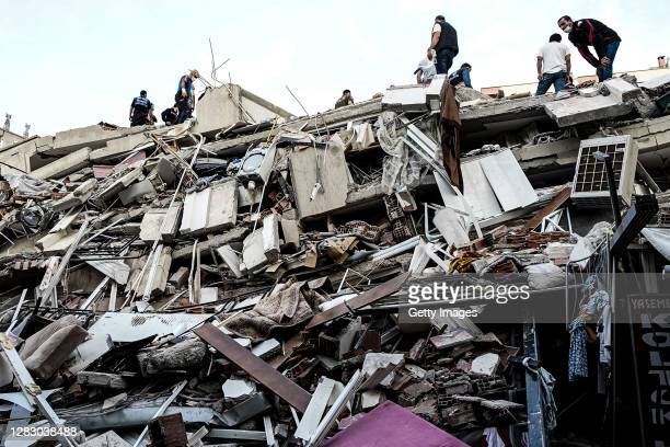Emergency services personnel search a collapsed building for survivors after a powerful earthquake struck on October 30, 2020 in Izmir, Turkey. Six...