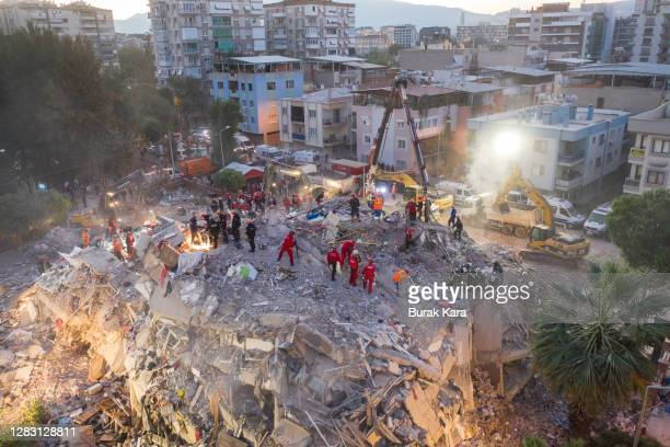 Emergency services personnel search a collapsed building for survivors the day after a powerful earthquake struck on October 31, 2020 in Izmir,...