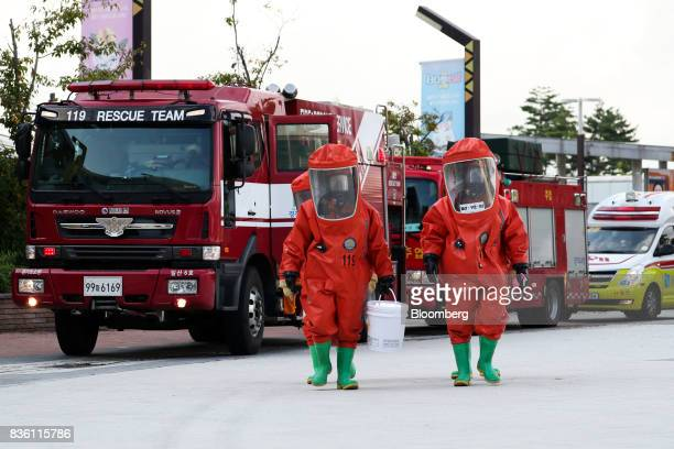 Emergency services personnel wearing protective clothing take part in a simulated chemical terrorism crisis during an antiterror drill on the...