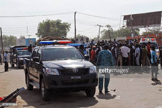Emergency services police and residents gather at the scene of a suicide bomb attack on a market in Maiduguri after two girls approximately seven or...
