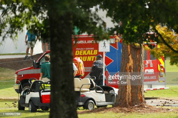 Emergency services provide assistance next to a tree damaged by a lightning strike during a suspension in play of the third round of the TOUR...
