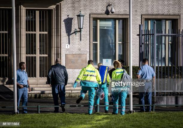Emergency Services staff walk toward the International Criminal Tribunal for the former Yugoslavia in The Hague on November 29 2017 The United...