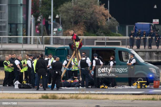 Emergency services surround protestors from the movement Black Lives Matter after they locked themselves to a tripod on the runway at London City...