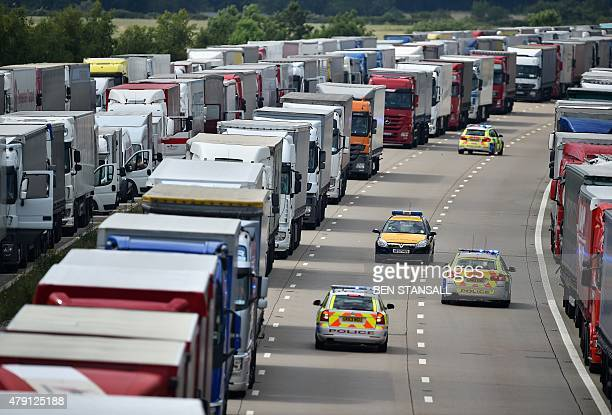 Emergency services vehicles patrol between parked trucks stacked on both northbound and southbound carriageways of the M20 motorway near Ashford in...