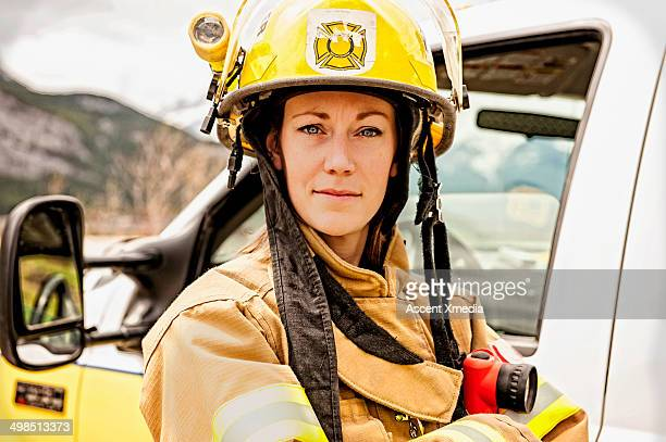 emergency services work stands beside fire truck - firefighter stock pictures, royalty-free photos & images