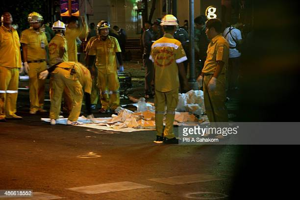 Emergency services workers collect human body parts at the scene of an explosion at Erawan shrine in Bangkok The bombing at Bangkok's Erawan shrine...