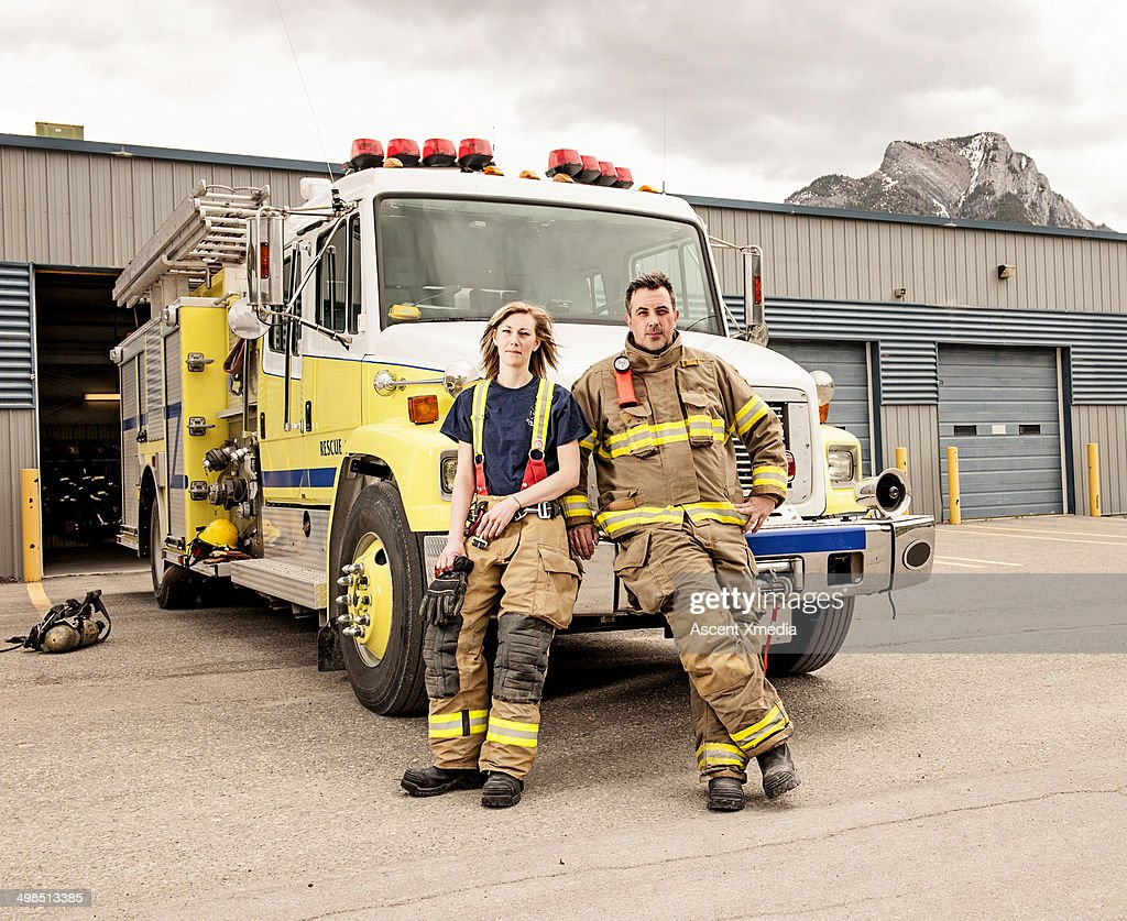 Emergency services workers sit on fire truck grill : Stock Photo
