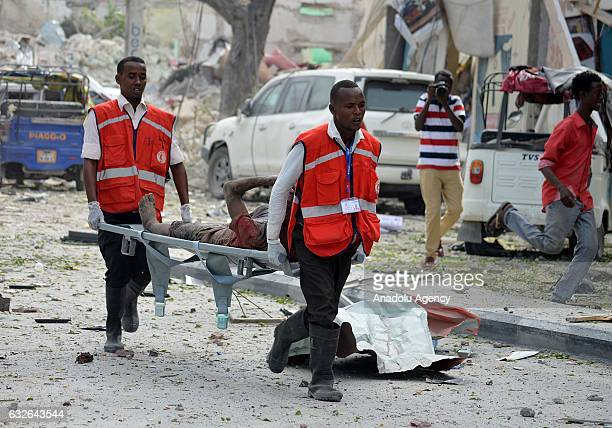 Emergency staff carry a wounded person after a bomb attack near Dayah Hotel where also hosts Somali government officials in Mogadishu Somalia on...