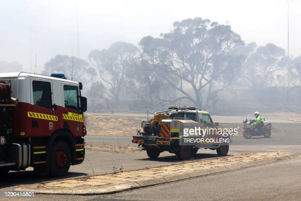 Emergency vehicles patrol the perimeter while battling a bush fire in Kwinana, some 30 kilometres south of Perth on January 4, 2021.