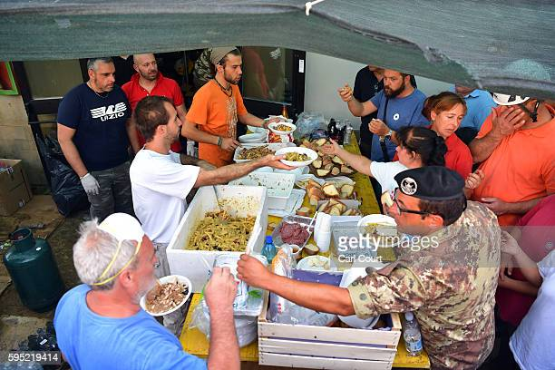 Emergency workers and earthquake victims are given food at a field kitchen on August 25 2016 in Amatrice Italy The death toll in the 62 magnitude...