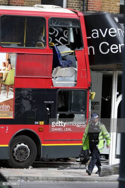 Emergency workers and officials examine the scene of an accident where a London bus ploughed into a shop on a busy street in southwest London on...