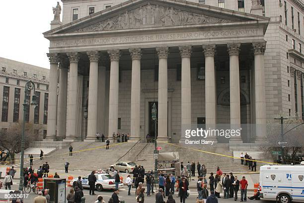 Emergency workers and pedestrians look at a car that crashed into the base of the steps of the state Supreme Court building in downtown Manhattan...