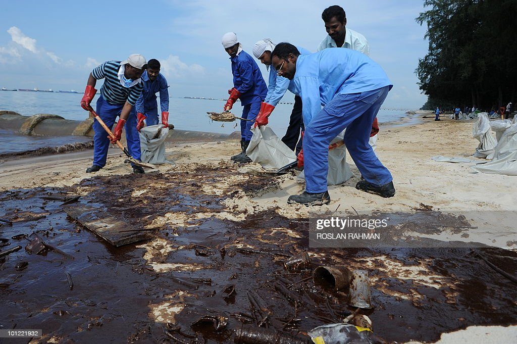 Emergency workers clear crude oil that washed up on the beach from a slick in Singapore on May 28, 2010. Singapore's most popular beach stretch remained shut to the public on the first day of the summer school holidays as emergency crews pressed on with their cleanup of an oil slick.