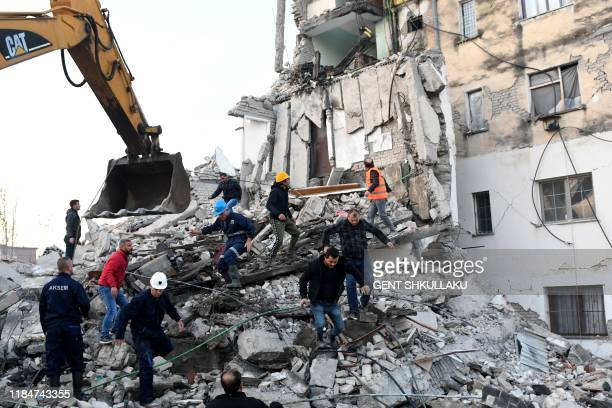 TOPSHOT Emergency workers clear debris at a damaged building in Thumane 34 kilometres northwest of capital Tirana after an earthquake hit Albania on...