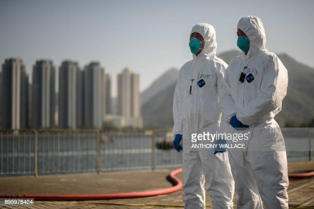 Emergency workers dressed in protective suits stand near a radiation level checkpoint as part of an interdepartmental Daya Bay Contingency Plan...