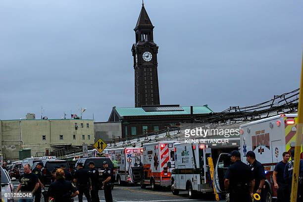 Emergency workers gather at New Jersey Transit's rail station in Hoboken New Jersey September 29 2016 A packed commuter train crashed into a station...