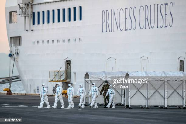 Emergency workers in protective clothing exit the Diamond Princess cruise ship at Daikoku Pier where it is being resupplied and newly diagnosed...
