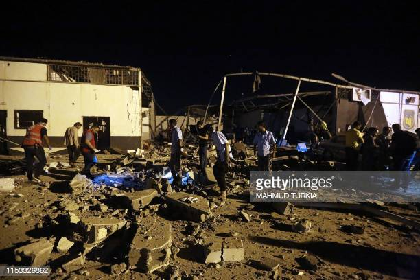TOPSHOT Emergency workers recover bodies after an airstrike killed nearly 40 at Tajoura Detention Center east of Tripoli on early July 3 2019 Nearly...