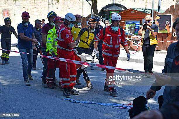 Emergency workers remove a body from a building that was destroyed during an earthquake on August 25 2016 in Amatrice Italy The death toll in the 62...