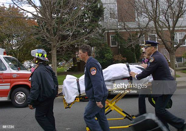 Emergency workers remove an injured man from the American Airlines flight 587 crash site November 12 2001 in Rockaway Beach New York City The plane...
