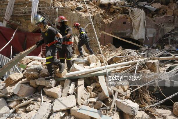 Emergency workers search a collapsed building on August 6, 2020 in Beirut, Lebanon. On Thursday, the official death toll from Tuesday's blast stood...