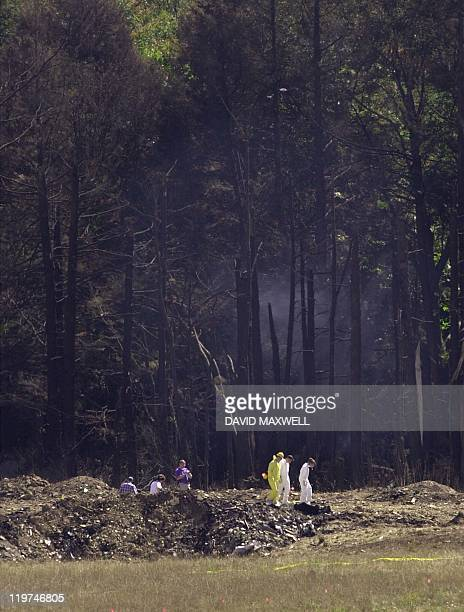 Emergency workers search the crash site of United Airlines Flight 93 in Shanksville Pennsylvania 12 September 2001 The hijacked plane crashed killing...
