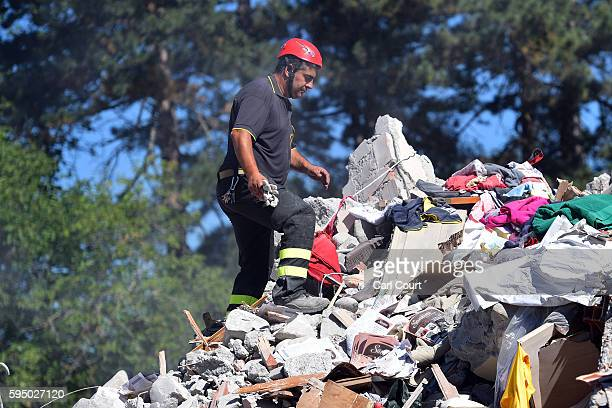 Emergency workers search the rubble of a building that was destroyed during an earthquake, on August 25, 2016 in Amatrice, Italy. The death toll in...