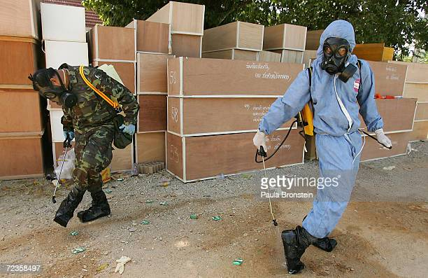 Emergency workers spray disinfectant on their shoes near the many coffins stacked at the Thap Lamu temple which has become a makeshift morgue for...