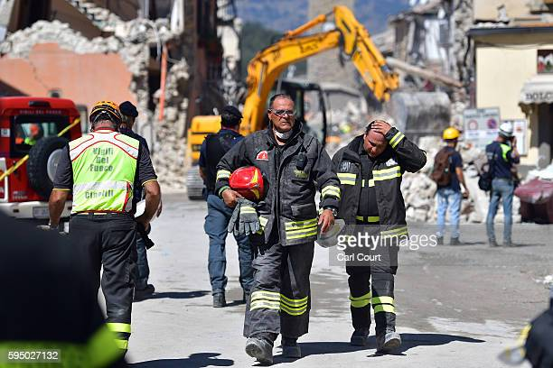 Emergency workers walk from buildings that were destroyed during an earthquake on August 25 2016 in Amatrice Italy The death toll in the 62 magnitude...