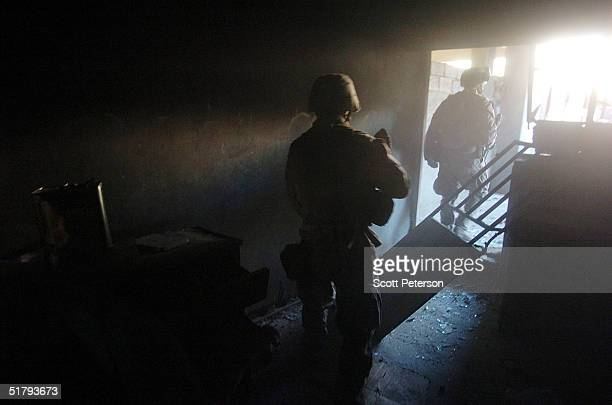 Emerging from a burnt out house US Marines of the 1st Light Armored Reconnaissance company as part of 1st Battalion 3rd Marines clear and search...