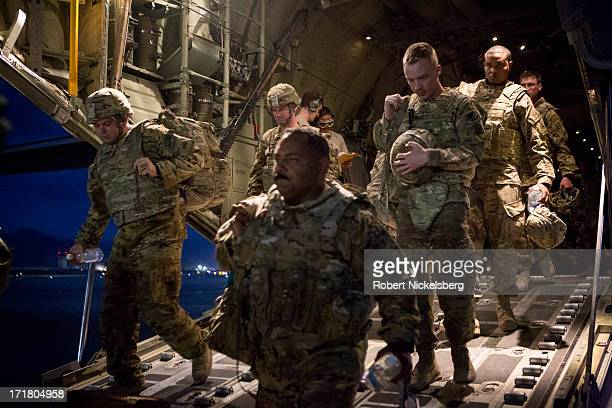 Emerging from a C-130 transport, U.S. Army soldiers arrive May 10, 2013 at Bagram Air Base, Afghanistan to begin their 9-month deployment. They will...