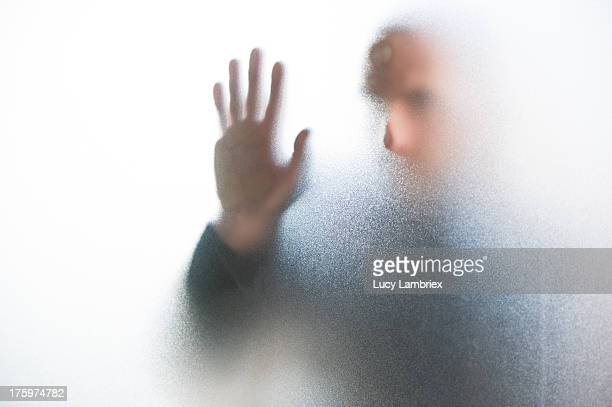 emerging man behind glass - translucent stock pictures, royalty-free photos & images