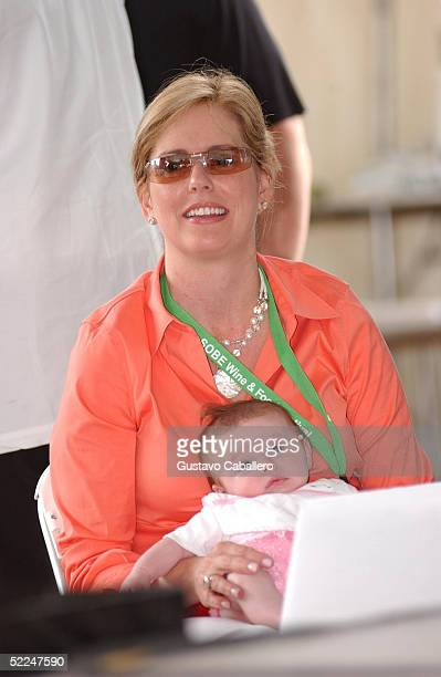 Emeril Lagasse's wife Alden Lovelace watches with their baby at the South Beach Food And Wine Festival on February 26 2005 in Miami Beach Florida