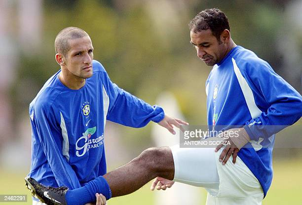 Emerson da Rosa of the Italian team Roma stretches assisted by his teammate Juliano Belletti of the Spanish team Villarreal on September 04 in...