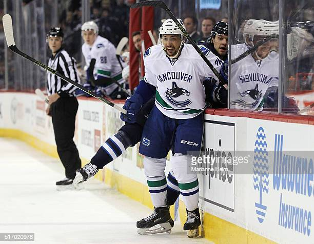 Emerson Etem of the Vancouver Canucks and Ben Chiarot of the Winnipeg Jets collide against the boards in second period action in an NHL game at the...