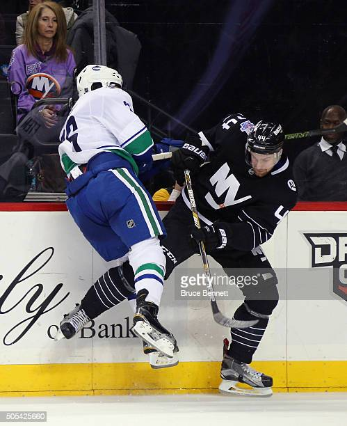 Emerson Etem of the Vancouver Canucks and Calvin de Haan of the New York Islanders collide during the third period at the Barclays Center on January...