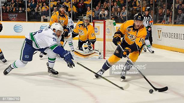 Emerson Etem of the Vancouver Canucks reaches for a puck controled by Mattias Ekholm of the Nashville Predators during the second period at...